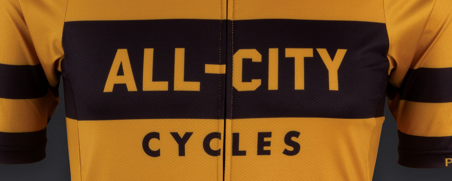 Close-up of Logowear Jersey design, All-City Cycles block font logo on mustard color jersey material