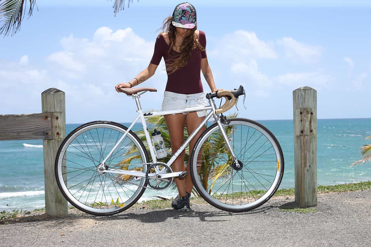 Woman in maroon shirt stands in front of ocean background with tan All-City Gonzo seat on white bike
