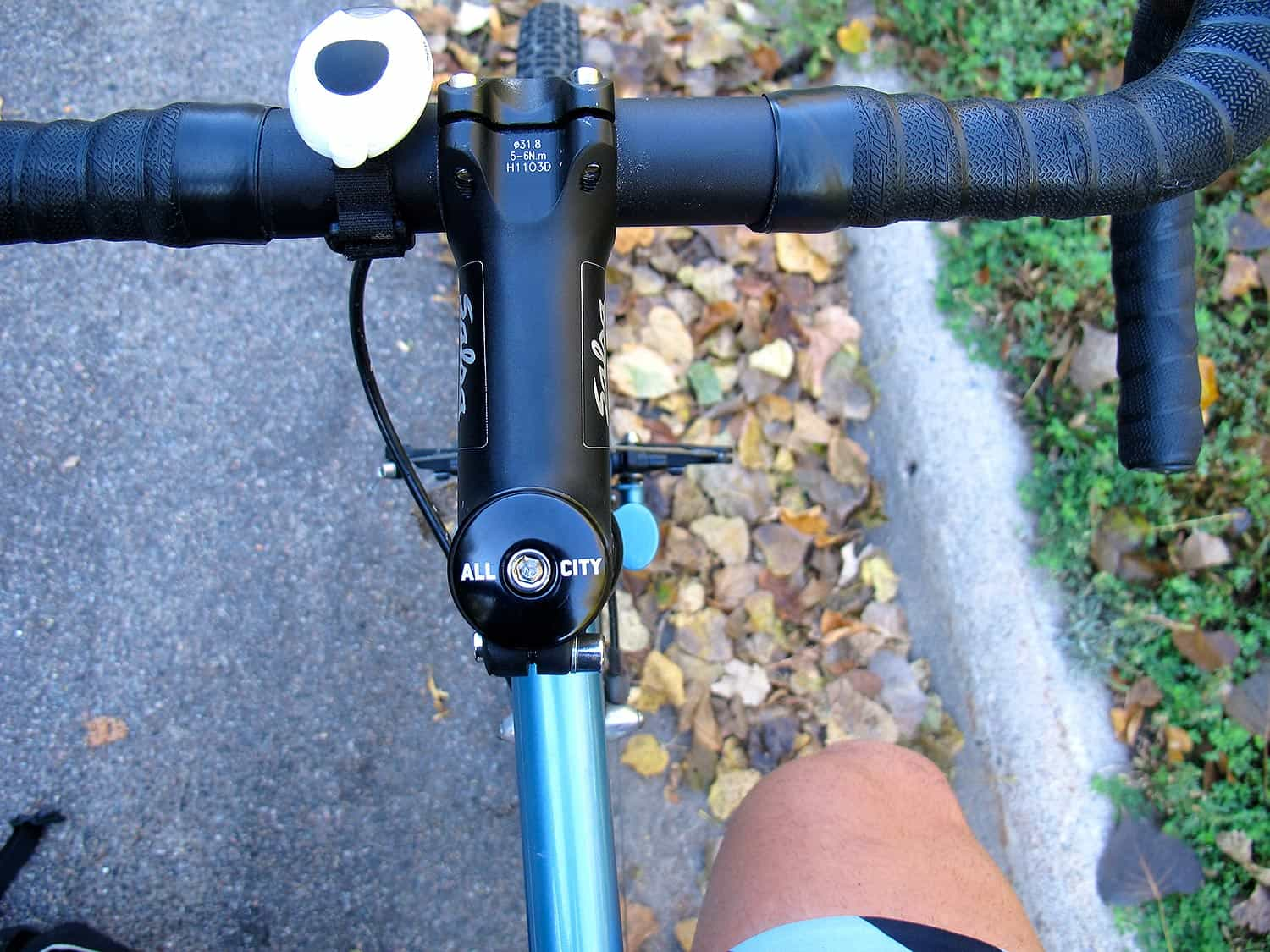 Black All-City Top Cap on blue bike with black handlebars on trail background
