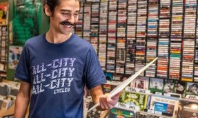 Person wearing Blue All-City flow motion t-shirt in record store