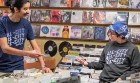 Two people wearing Grey All-City Flow Motion crewneck sweatshirts in a record shop
