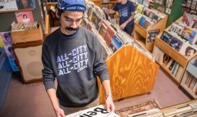 Person wears Grey All-City Flow Motion crewneck sweatshirt as they look through records