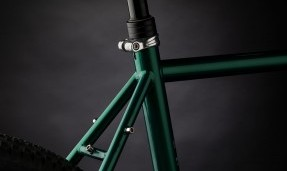 Close up of polished silver All-City Shot Collar on green bike with black background