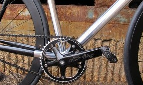 Black All-City 612 Track Ring close up on silver bike with outdoor background