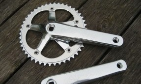 Polished silver All-City 612 Track Crank product side view on wood background