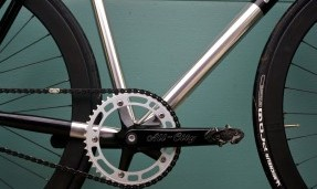 Polished silver All-City 612 Track Crank on silver bike with green background