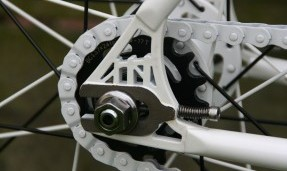 Black All-City Standard Cog on white bike frame close up view