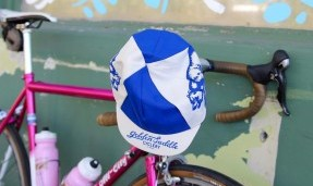 blue and white All-City Cycles Cali Cap on red bike handles
