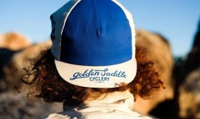 Person wearing blue and white All-City Cycles Cali Cap outside, back view