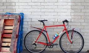 Black and red All-City bike with foldable fender against a white wall