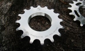 Polished silver All-City Stainless Cogs on wood background