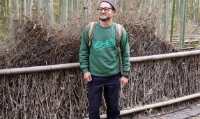 Person wearing a green throwback crewneck sweatshirt with outdoor wall background