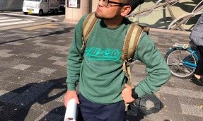 Person wearing a green throwback crewneck sweatshirt with outdoor background