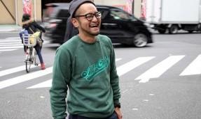 Person wearing a green throwback crewneck sweatshirt while crossing cross walk