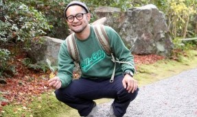 Person wearing a green throwback crewneck sweatshirt while squatting outdoors