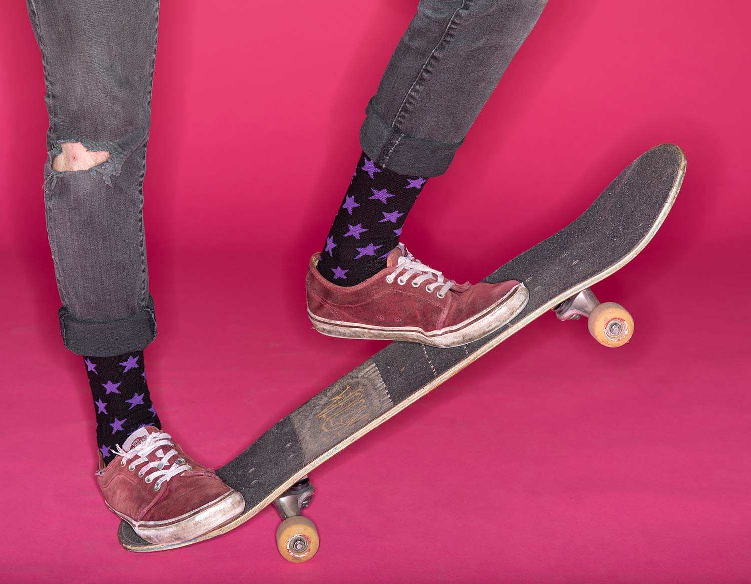 Person wearing black let's Go Crazy Socks while skateboarding on pink background