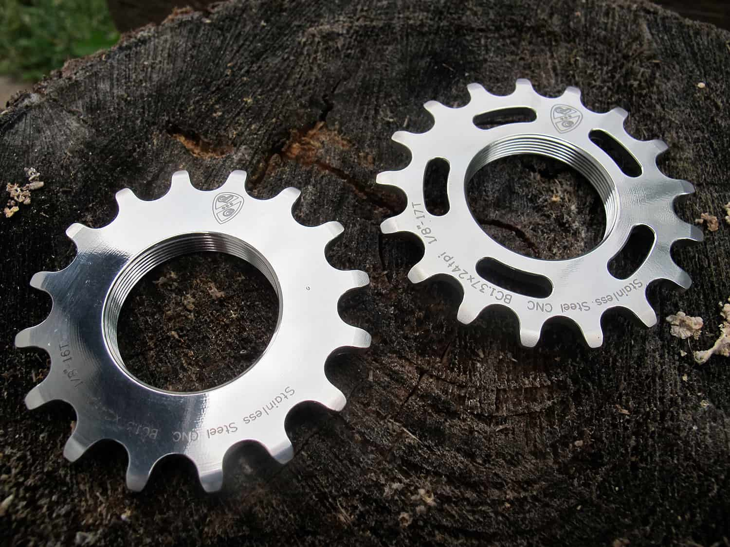 Two polished silver All-City Stainless Cogs on wood background