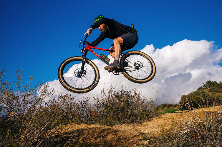 Mountain biker on All-City steel mountain bike catching air off jump blue sky and clouds in background