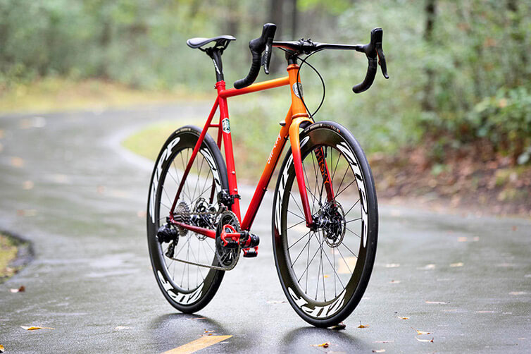 All-City Zig Zag steel road bike, orange, propped up on wet paved trail in forest