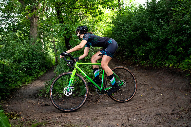 Cyclist in helmet and cycling apparel riding an off-road trail in forest on All-City steel cyclocross bike