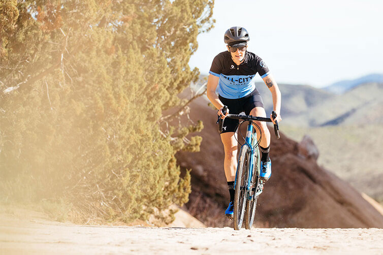Cyclist in helmet, sunglasses and cycling apparel riding an All-City steel all road bike on a gravel fire road