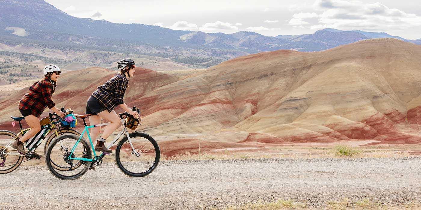 Two cyclists riding Gorilla Monsoon bikes up remote desert gravel road in the mountains, out of the saddle