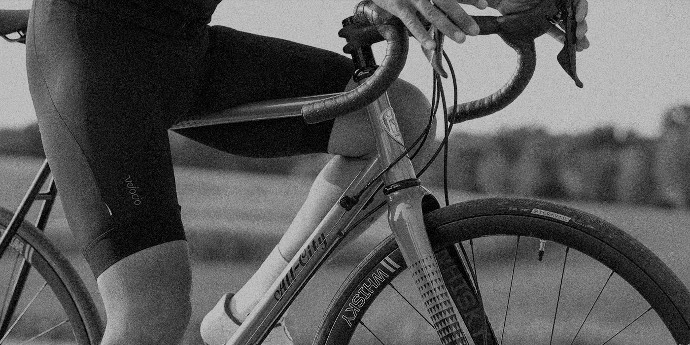 Person in cycling shorts standing over All-City Zig Zag bike with foot down showing bike side view, black and white